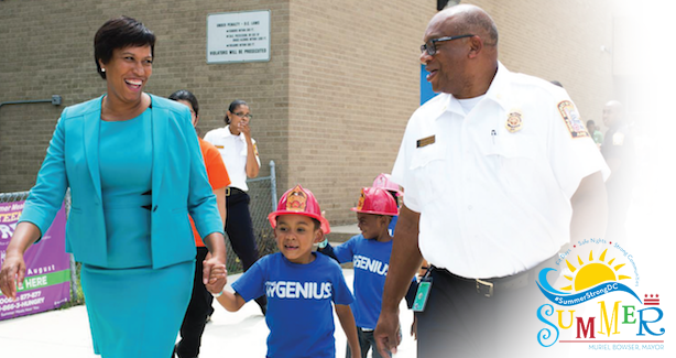 Mayor Bowser and a fireman holding a small child's hands